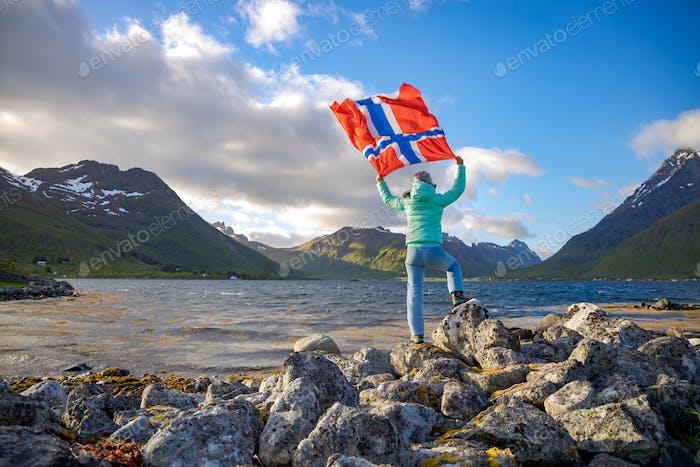 Frau mit einer winkenden Flagge von Norwegen auf dem Hintergrund der Natur