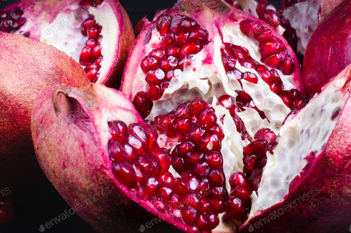 Thumbnail for Ripe juice pomegranate fruit on black background - whole and cut, top view