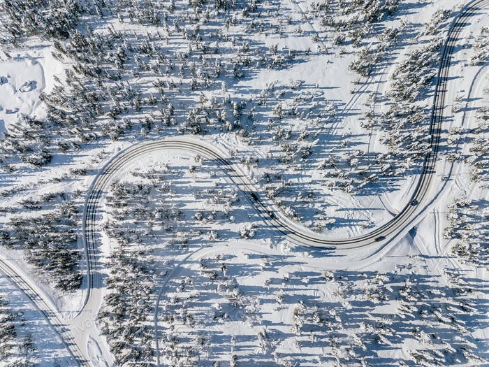 Aerial view of snowy and frozen winter road. Winter landscape with snow covered trees in Finland.
