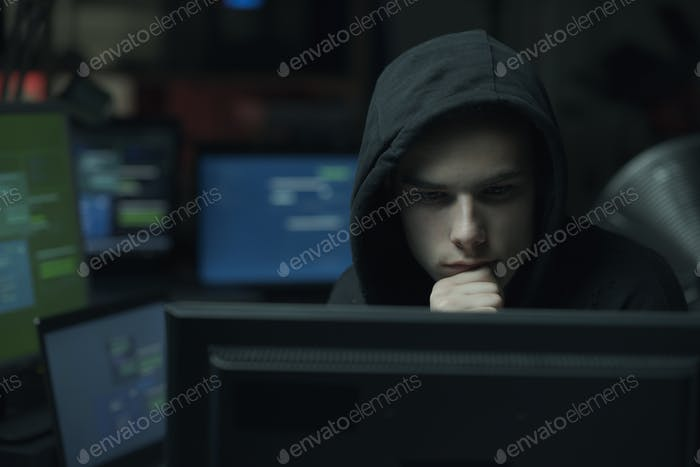 Cool hacker with hoodie working with computers
