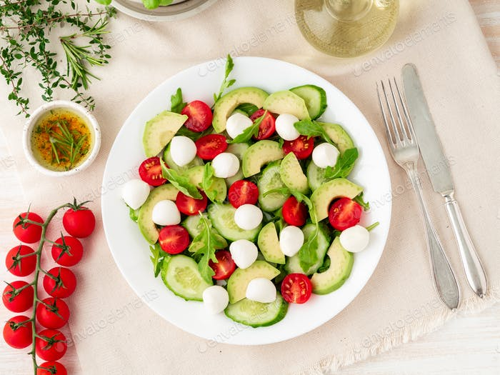 Fresh salad with tomatoes cucumbers arugula mozzarella and avocado. Oil with spices, top view