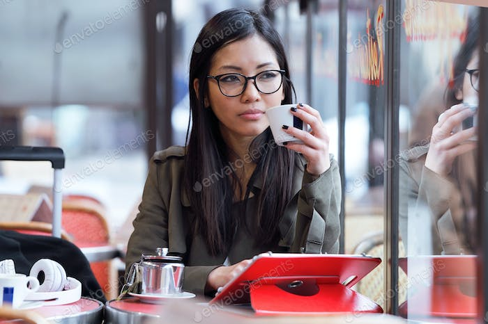 Beautiful young asian woman using her digital tablet while drink