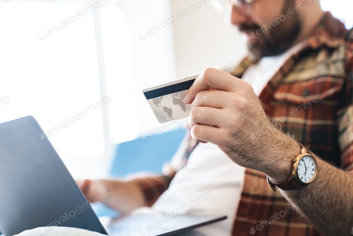 Portrait of young man using laptop and credit card on sofa at home