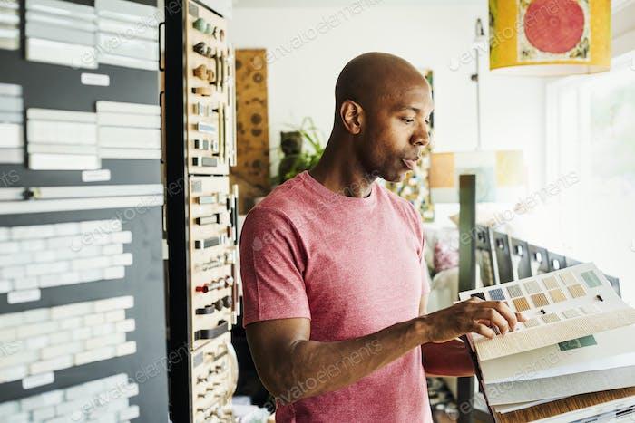 Mann, der sich ein Musterbuch in einem Innenarchitekturgeschäft anschaut. Fliesenproben an den Wänden.