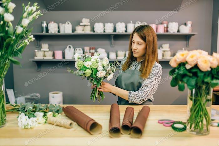 Female florist decorate fresh flower composition