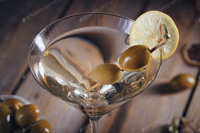 Glass of martini with green olives