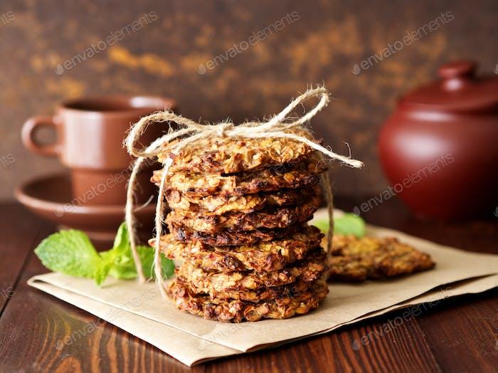 Hausgemachte Haferflocken Kekse mit Banane, Hafer, Nüssen, Eiern und Mehl frei auf braunem dunklem Holz