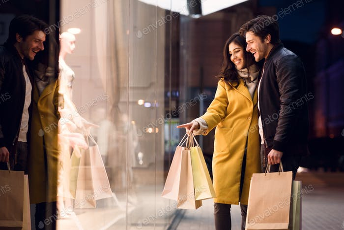 Window shopping. Couple looking at fashion store's showcase