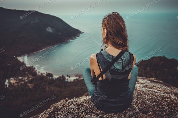 junge Frau sitzt auf Stein und schaut auf die Küste