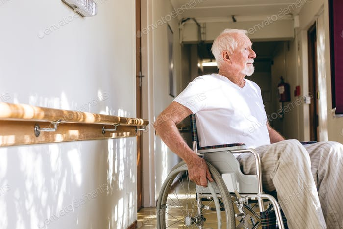 Side view of senior Caucasian male patient sitting in wheelchair in corridor at retirement home