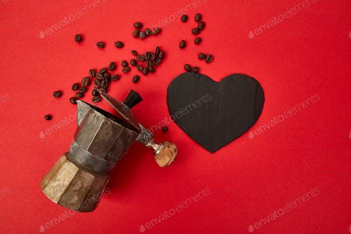 Flache Lage von Kaffeemaschine und Kaffeebohnen auf rotem Hintergrund.