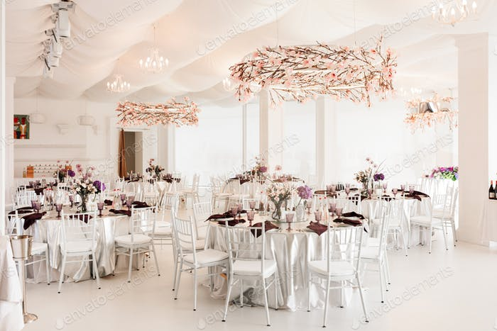 Amazing floral decorated white wedding hall with tables