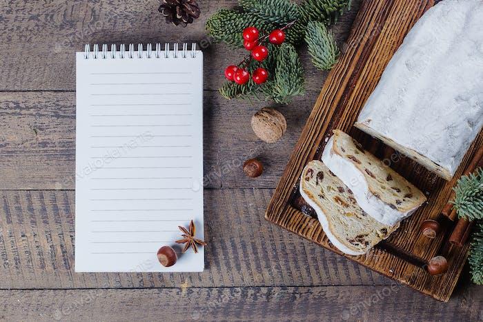 Traditionelles Weihnachtsfest Gebäck Dessert Stollen mit festlicher Dekoration und Notizbuch weiß