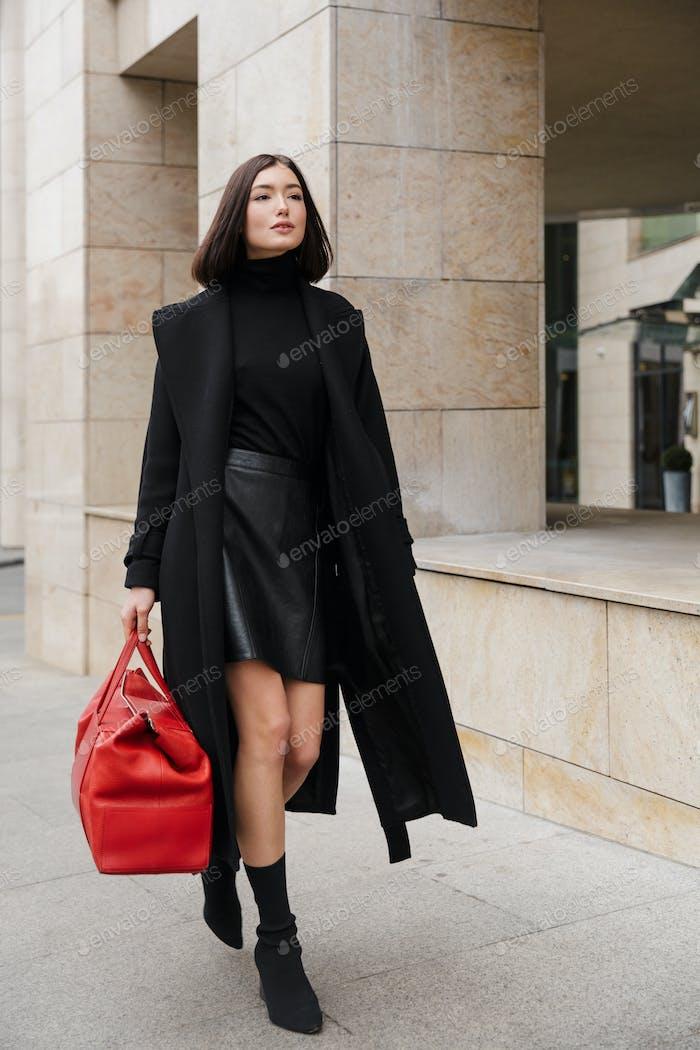 Attractive young brunette woman wearing autumn coat walking