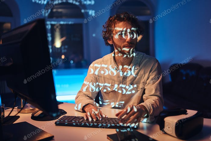 Serious office worker looks at camera typing on computer keyboard