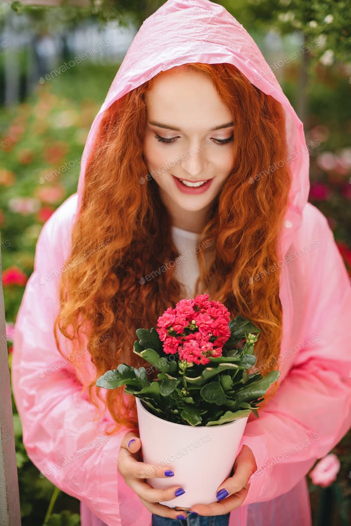 Smiling lady with redhead curly hair standing in pink raincoat and holding beautiful flower