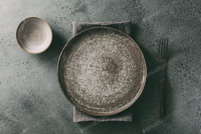 Flat ceramic plate, small cup and fork on stone surface