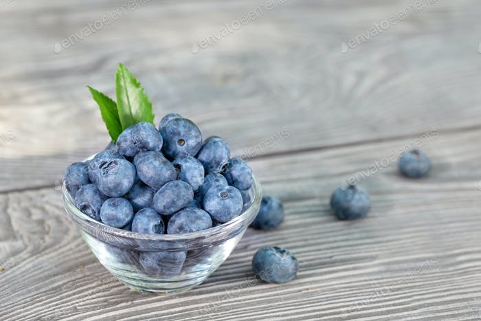 Blueberries in glass bowl on a wooden table