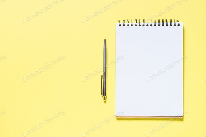Notebook, pen and smartphone on yellow