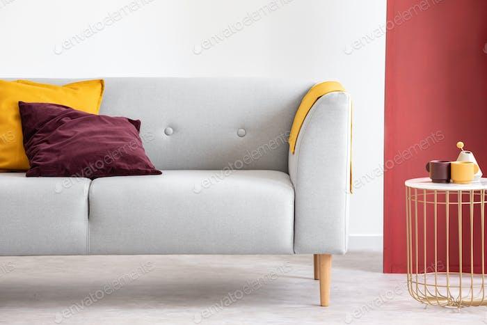 Lila und orange Kissen auf grauem Sofa neben Tisch in grau und