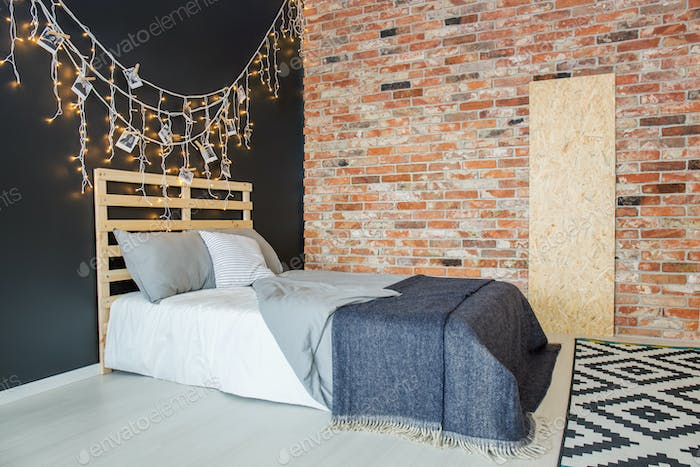 Bed in bedroom with brick wall