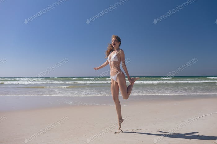 Attractive Caucasian woman standing on tip toe at beach on a sunny day.