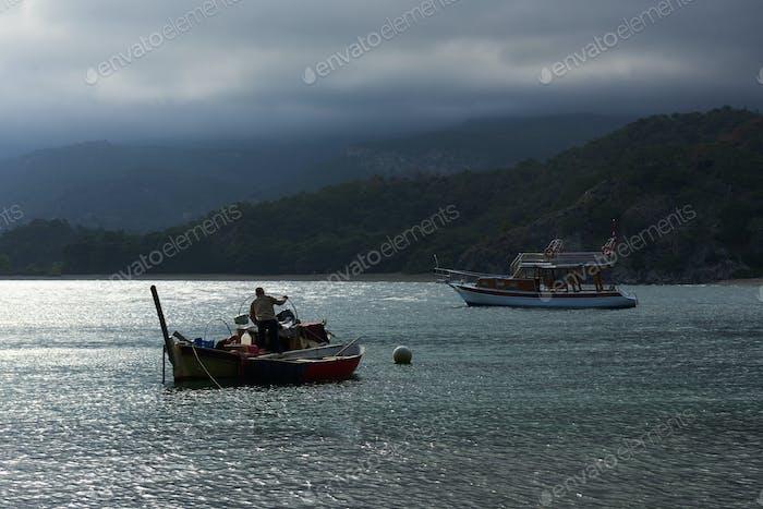 Boats sail on a rainy day, gloomy sky in Turkey