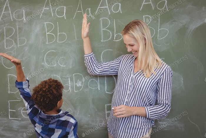 Happy teacher and schoolboy giving high five in classroom