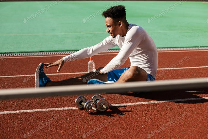 Handsome African American sportsman stretching on racetrack during workout at city stadium