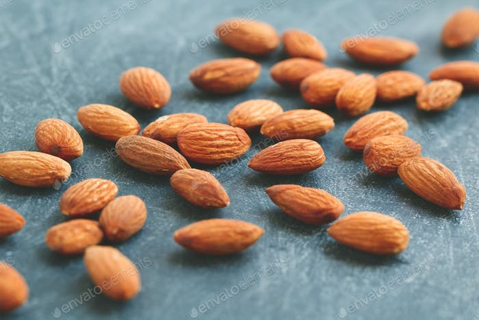 Almond nuts over grey background. The concept of healthy and organic food.