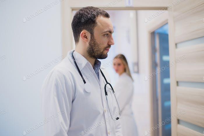 Traurige nachdenkliche Arzt Aufenthalt im Krankenhausgang