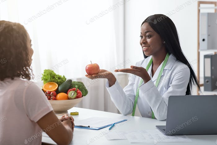 Positive african nutritionist recommending fresh fruits to eat