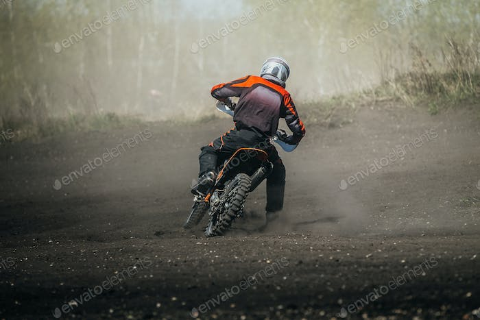 Racer motorcycle rides on dusty track