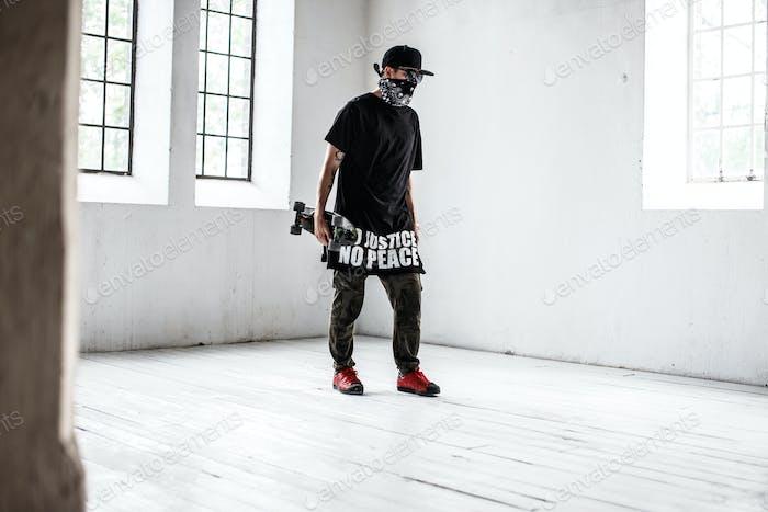 Skater in mask in big white room.