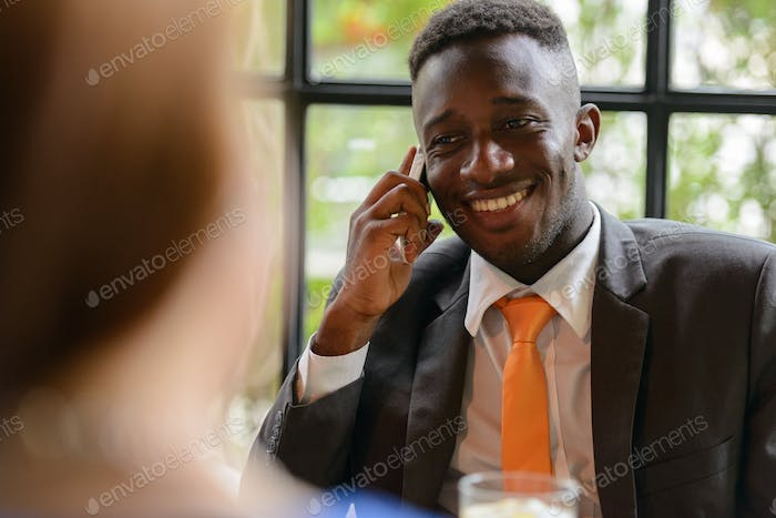 Young African businessman and young businesswoman together