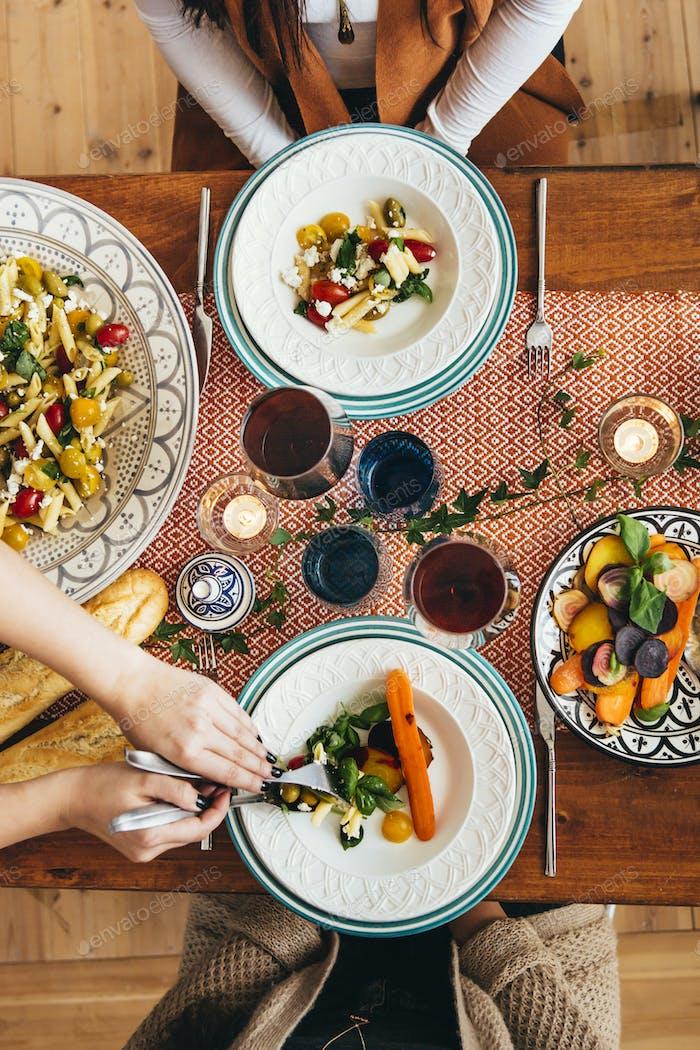 Abgeschnittenes Bild der Hände der Frau, die Essen an Freunde am Tisch serviert