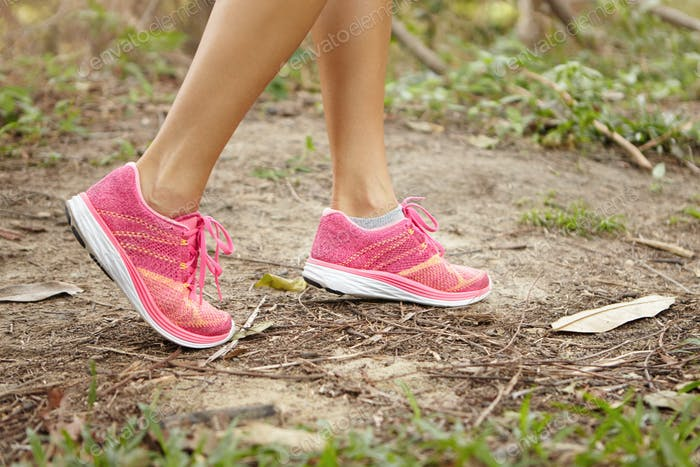Sports and adventure concept. Close up shot of female legs wearing pink running shoes in forest whil