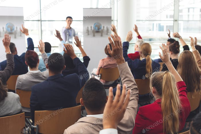 Business people raising hands at business seminar in office building