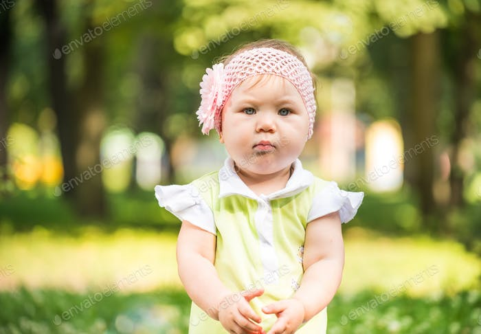 Small baby girl with flower in hair riding carousel outdoors