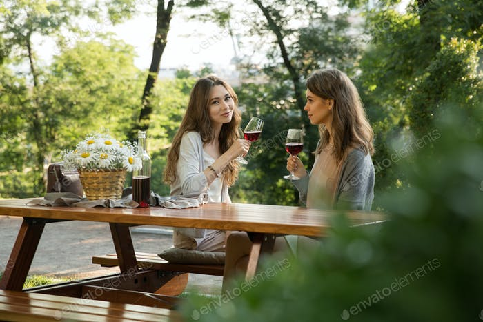 Pretty young two women sitting outdoors in park drinking wine