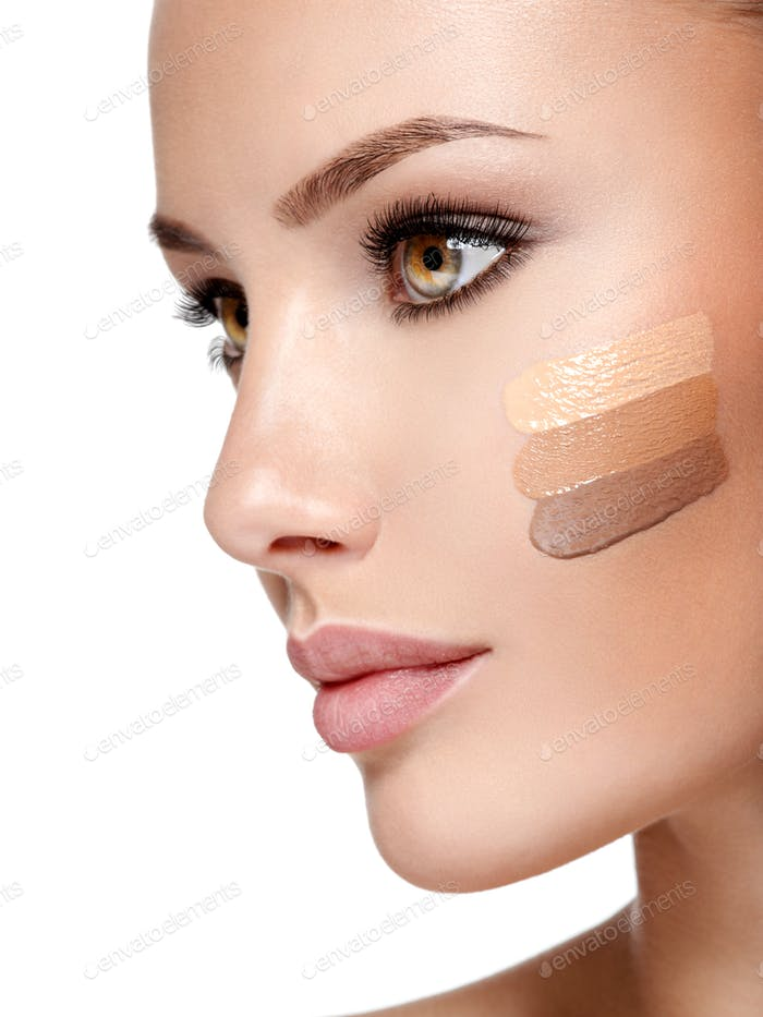 Beautiful face of  woman with cosmetic foundation on a skin.