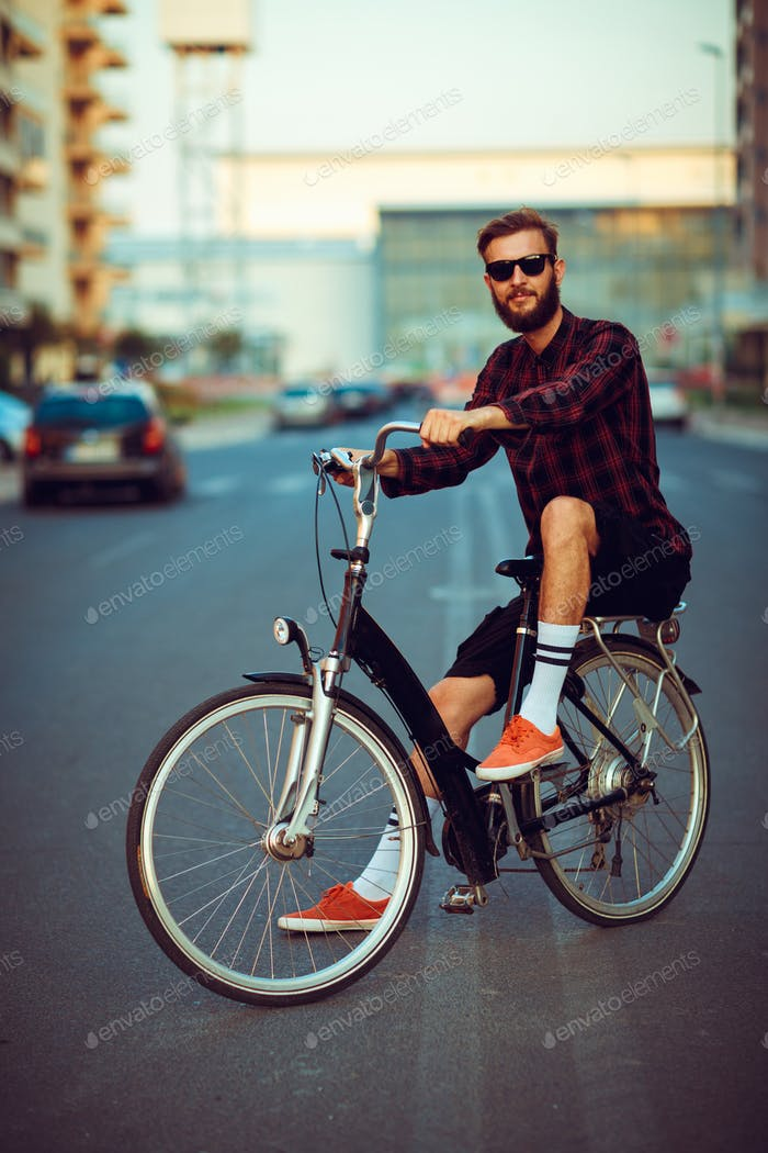 Stylish man in sunglasses riding a bike on city street