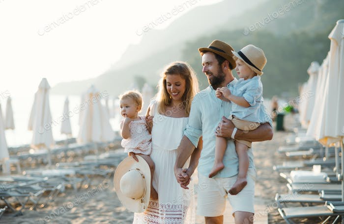 A young family with two toddler children walking on beach on summer holiday.