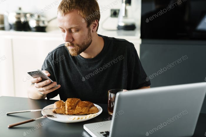 Photo of man using laptop and cellphone while having breakfast