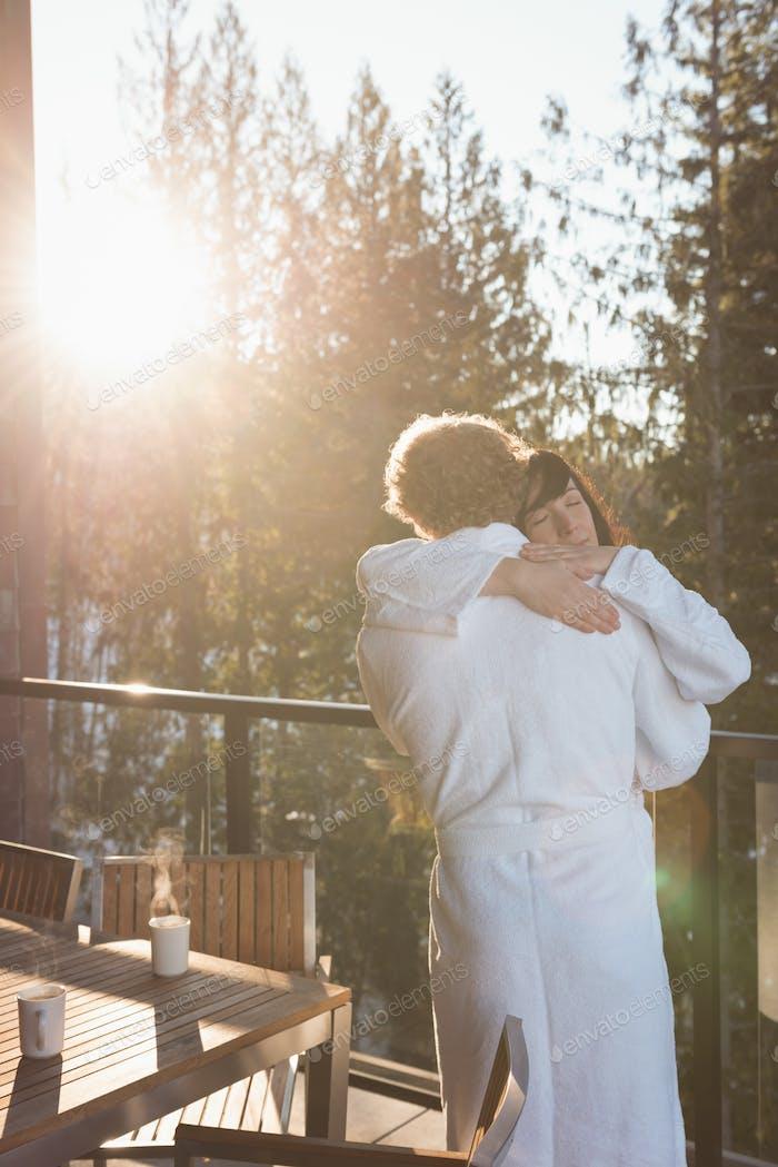Paar umarmt sich gegenseitig auf dem Balkon zu Hause