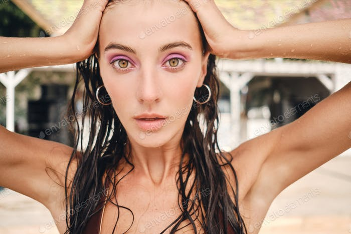 Beautiful brunette girl with wet hair thoughtfully looking in camera on beach