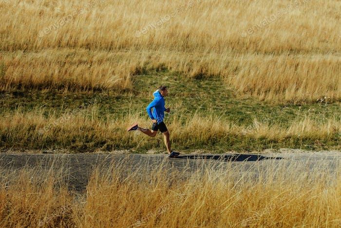 male runner running on asphalt road
