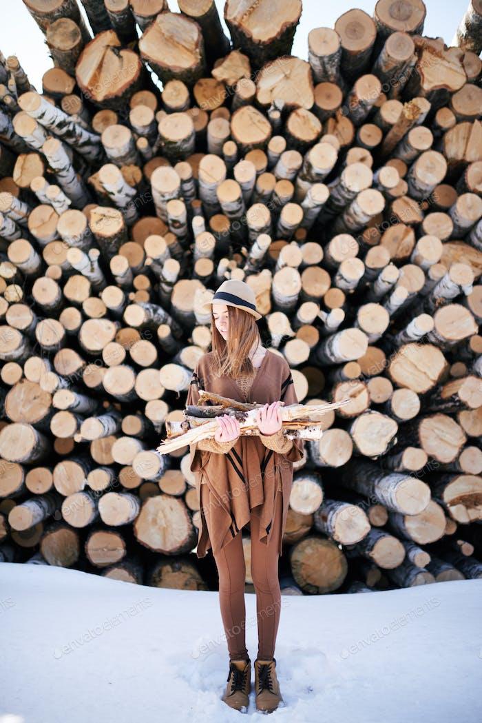 Mujer joven en traje marrón sosteniendo pila de leña para chimenea