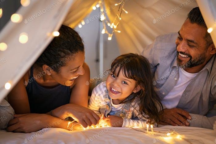 Glückliche ethnische Familie spielen zusammen in gemütlicher Hütte mit Tochter