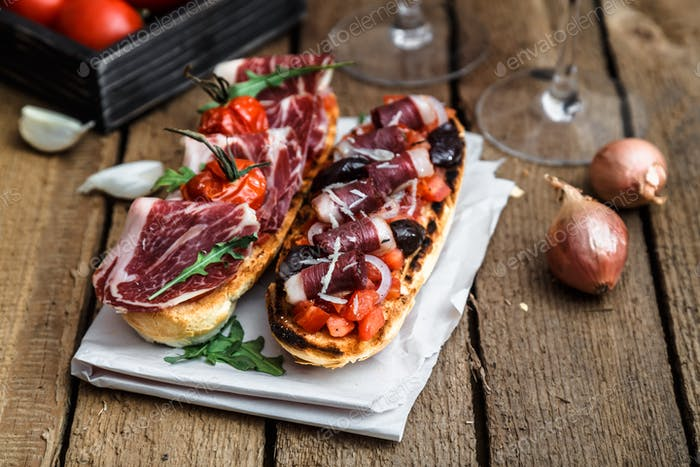 Traditional italian bruschetta with ham and wine